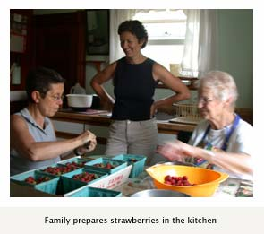 Family prepares strawberries in the kitchen